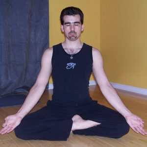 A man sitting cross-legged with his eyes closed and arms extended