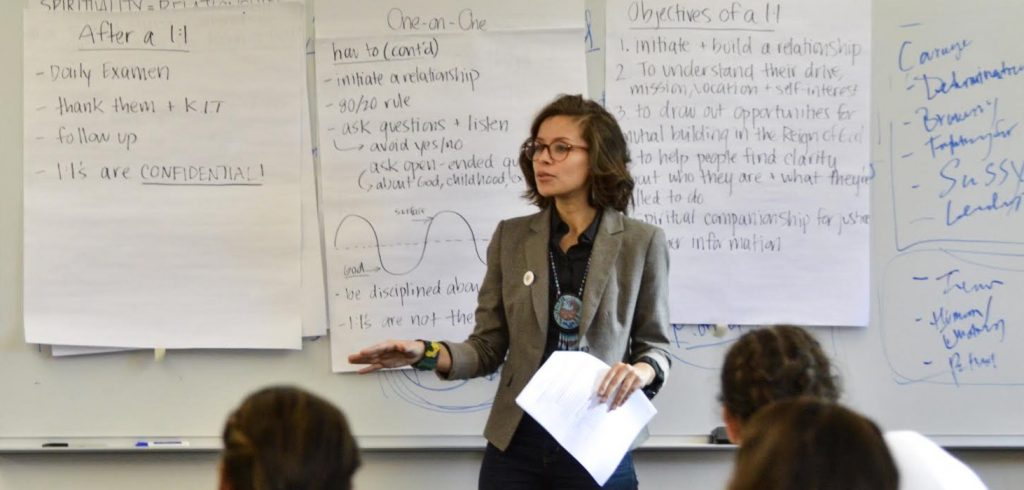 A woman wearing glasses and a gray blazer stands in front of a dry erase board with writing on it.