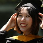 grad with hands adjusting cap