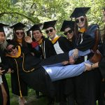graduates carrying another grad